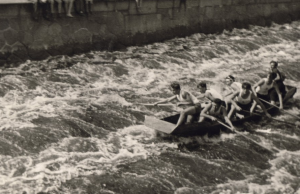 A crew in the 1948 regatta passing one of the main obstacles: the Helmovský weir