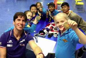 A group-selfie of Steve and Beaver Scouts displaying his gold medals