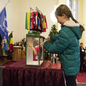 Melanie, this year's Friedenslichtkind, passes on the flame of the Peacelight to the official candle of the Scouts and Guides of Austria (image: EEUDF)